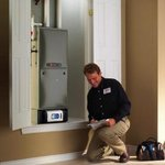 Serviceman tuning up furnace in home