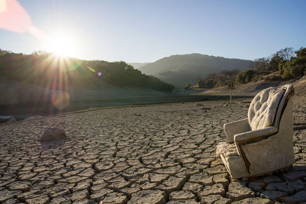 Easy chair outside on drought-cracked mud